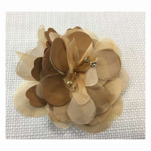 Vintage effect flower composed by different materials including also leather and organza