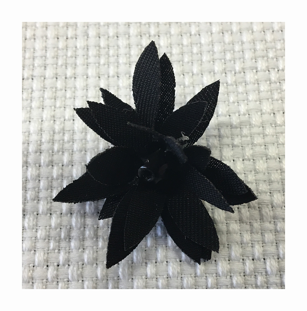 Edelweiss made in cut and laser treated different materials with a central bead.